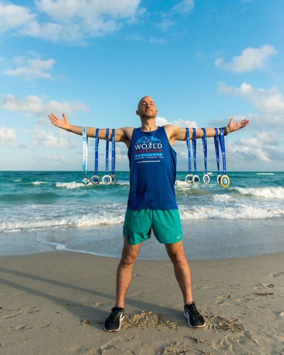 Jared Blank and his 7 medals, completing the World Marathon Challenge